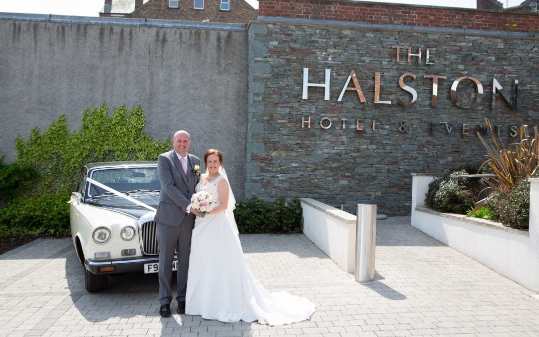 Bride and groom pose for photo outside The Halston, Carlisle