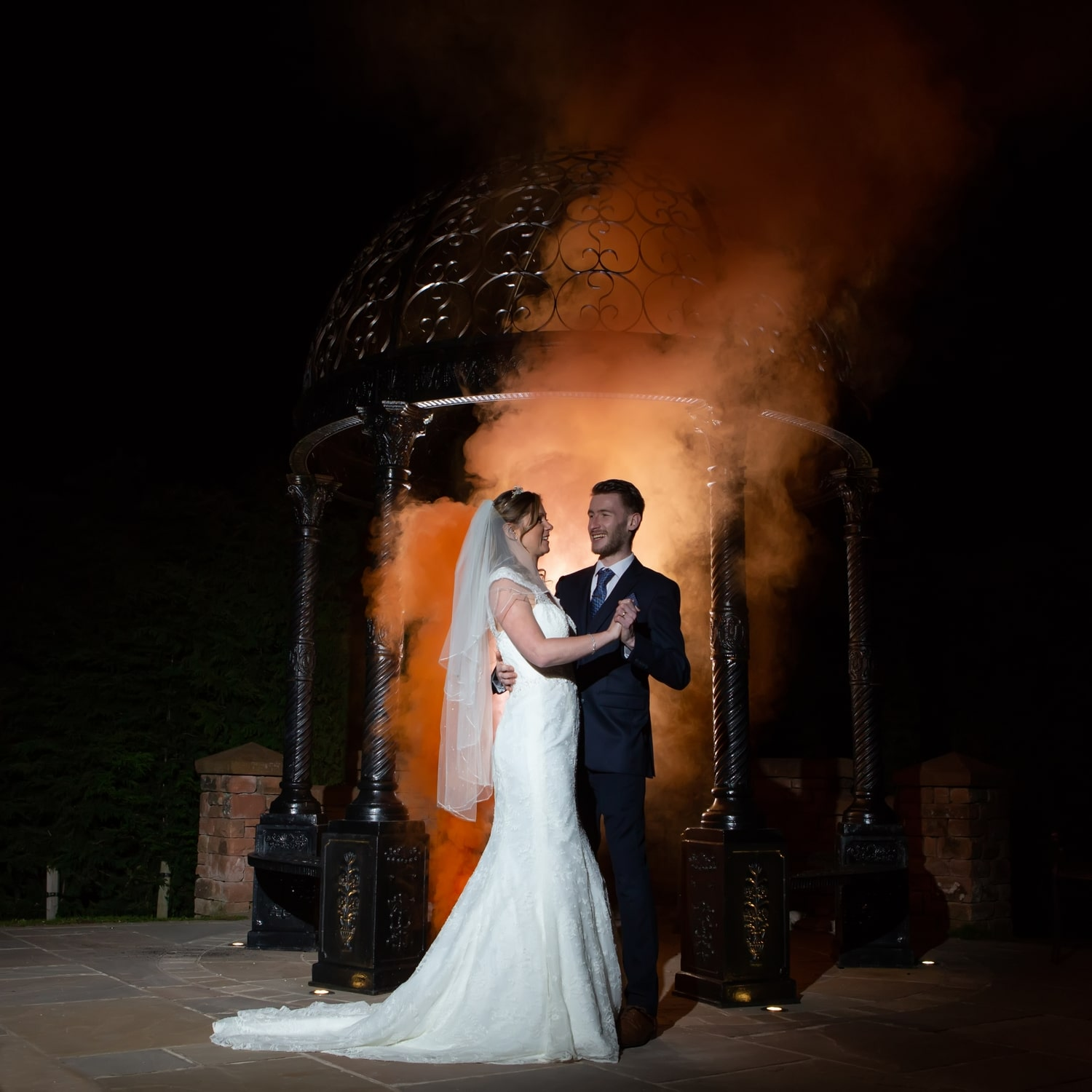 Bride and Groom outdoors holding each other at night, whilst behind orange smoke has been lit up to form a creative background.