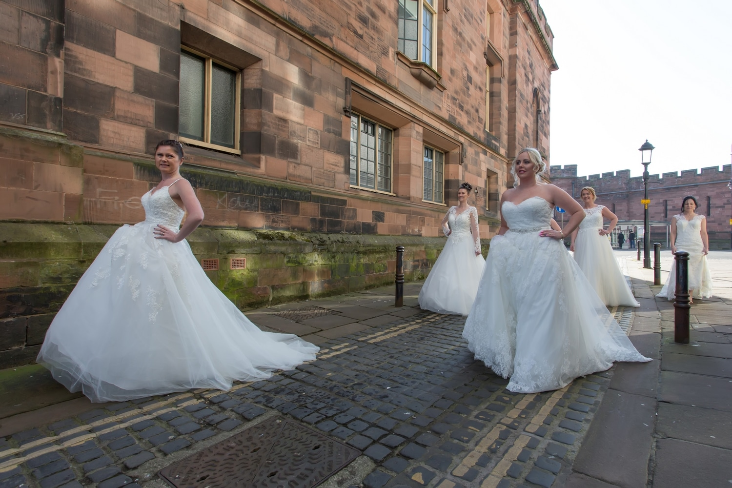 Five brides walking down a cobbled street in Carlisle
