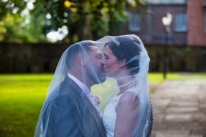 Bride and Groom Kissing Outside St Cuthbert's Church, Carlisle photographed by Keltic Rose Photography, a Carlisle and Cumbria Photographer