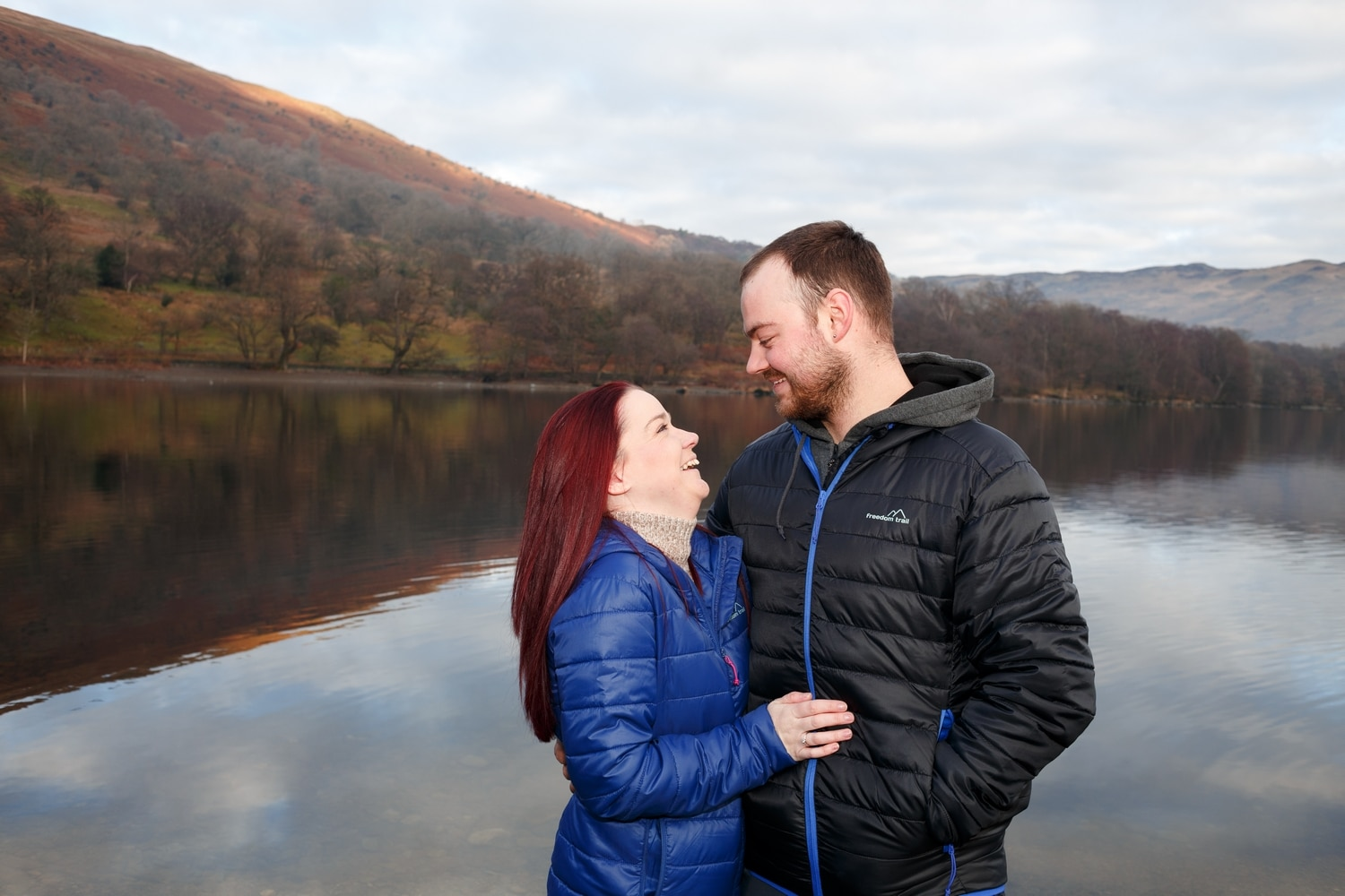couple look at each other with snow on the fells in the background