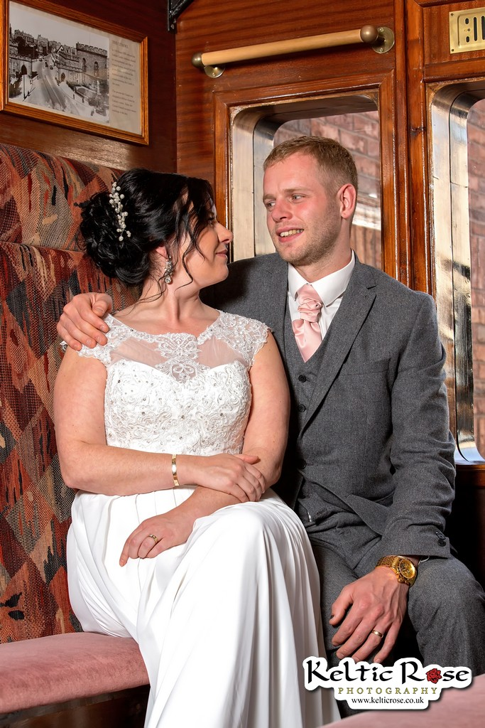 Wedding couple looking at each other in a railway carriage in Tullie House Carlisle