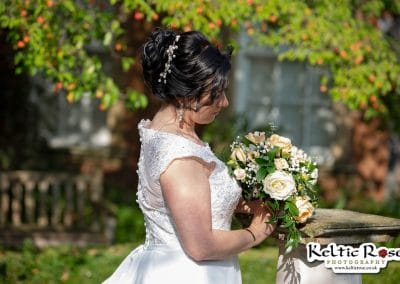 Bride looks down at her flowers at Tullie House Museum and Art Gallery