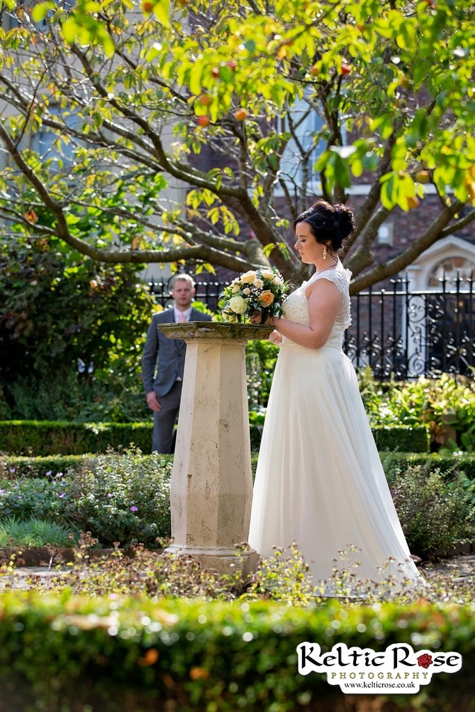 Bride at the Sundial at Tullie House Museum and Art Gallery with Groom in the background