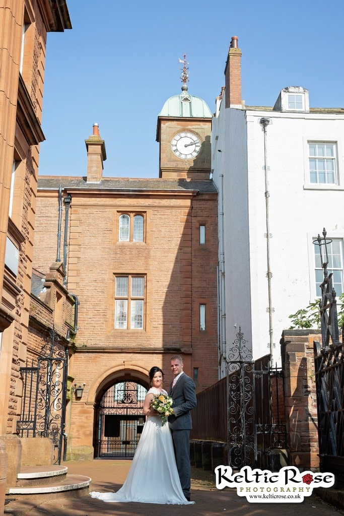 under the clock for wedding photographs at Tullie House Museum and Art Gallery Carlisle