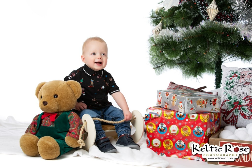 Little boy sitting on a sledge at Keltic Rose Photography Christmas Photo Session